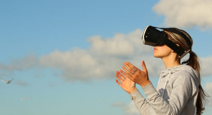 Frau trägt VR-Brille und hält die Hände hoch